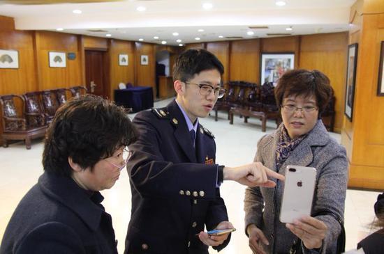 图为江北区税务局工作人员为纳税人辅导个人所得税APP的安装与应用。  江北区税务局供图