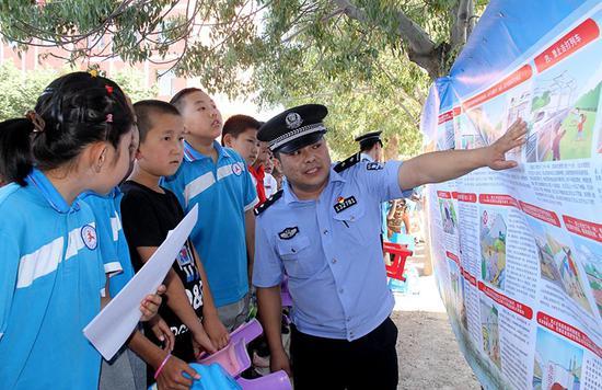 7月2日哈密站派出所民警在火箭農場學校給學生講解愛路護路宣傳掛圖。