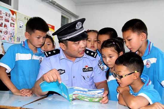 7月2日哈密站派出所民警在火箭農場學校教室里給學生上法制課。