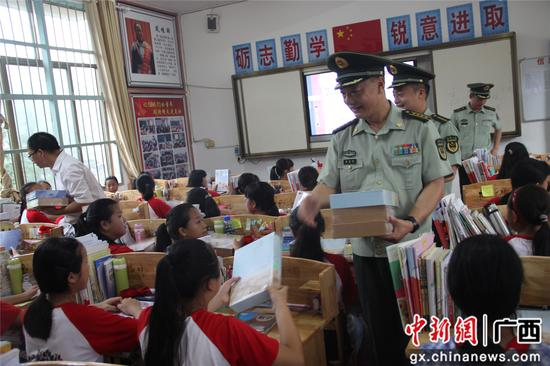 官兵们为红瑶女童班学生发放纪念品 。丁健 摄