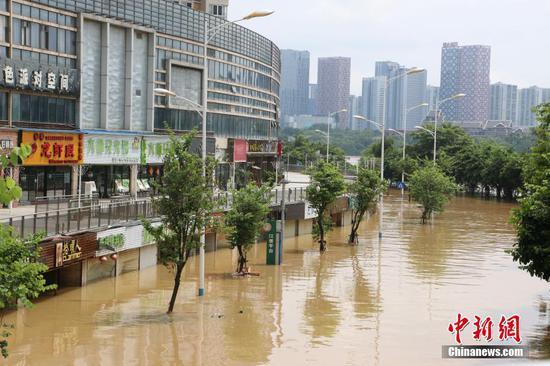 超警戒水位洪峰过境广西柳州 民众蹚水、乘船出行