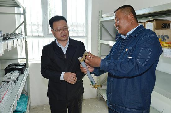 国网新疆电力党委书记、董事长李明看望慰问塔克什肯供电所所长王丛新。 (石怀平 摄)