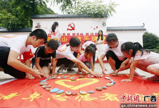 """广西科技大学""""三下乡""""学生正在与孩子们拼石头彩绘画图。韦荣军 摄"""