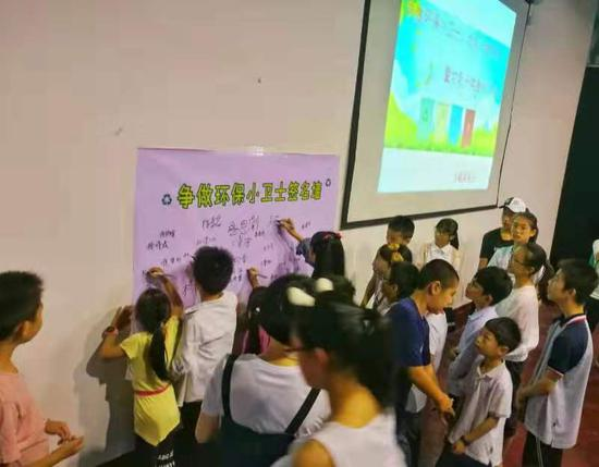 """孩子们在""""争做环保小卫士""""签名墙上签名。徐建婷摄"""