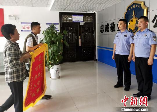 李軍(化名)夫婦為新疆兵團第一師阿拉爾市城區公安局刑警送錦旗。 趙慧 攝