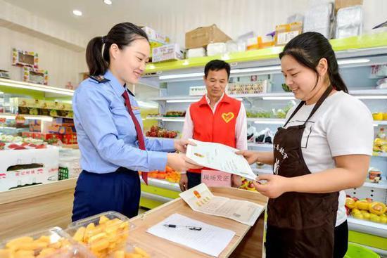 工作人员正在食品店现场办理食品经营许可证 谭云俸 摄