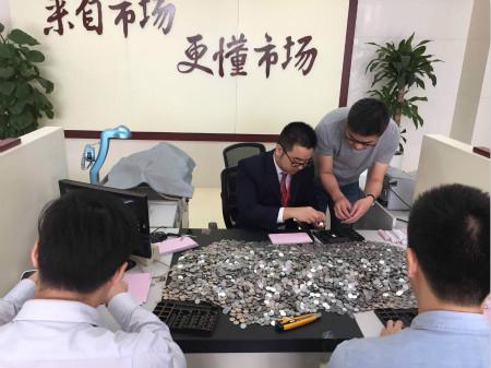 图为浙江稠州商业银行柜员们清点硬币。  浙江稠州商业银行供图