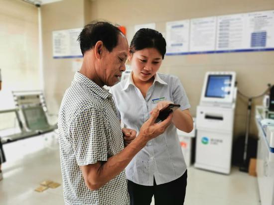 图为青田农商行工作人员为客户介绍app用法。 供图