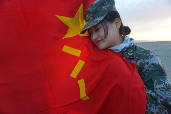 """图为官兵和""""八一""""军旗合影。"""
