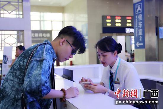图为桂林火车站工作人员耐心解答旅客问讯。常国思 摄