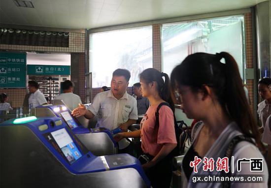"""图为桂林火车站工作人员引导旅客""""刷脸""""进站。常国思 摄"""