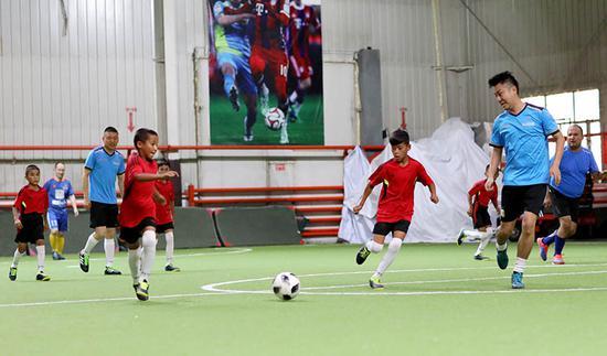 8月2日晚喀瓦克乡小学足球队抵达乌鲁木齐后,与南航新疆分公司足球协会的叔叔们踢了一场友谊赛。张思维摄