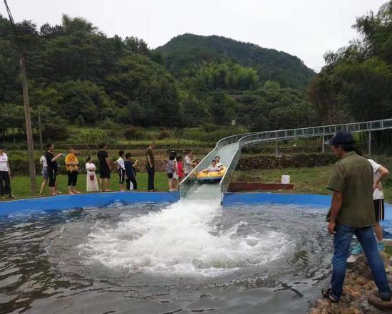 图为山林与田野间,游客享受金龙滑道项目。该村供图