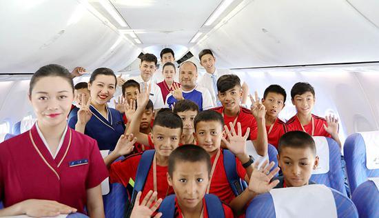 飞机上,足球队与南航乘务组合影。张思维摄