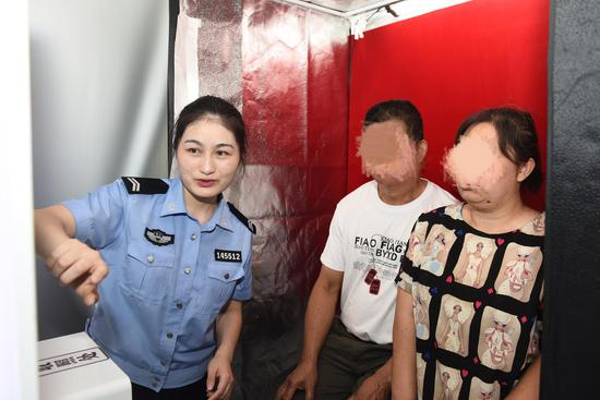 办证民警协助宋世萍夫妇拍摄结婚证照片。平湖公安提供