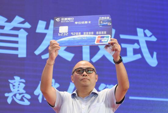 图为:一位企业代表展示起新获得的华夏小微卡。   王刚 摄
