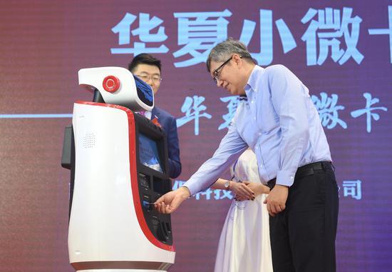 """图为:华夏银行新一代智能发卡机器人""""华小夏""""为客户发放华夏小微企业个人卡。   王刚 摄"""