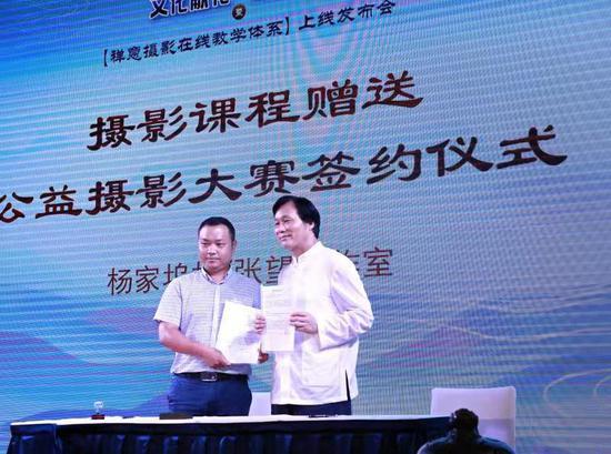 图为张望与杨家坞村村长寿立明举行课程赠送与公益摄影大赛签约仪式。 张望工作室供图