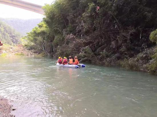 图为:永嘉消防指战员对下游河道进行搜寻