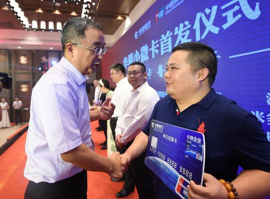 图为:中国银联机构合作部总经理单长胜为一位企业代表授卡。   王刚 摄
