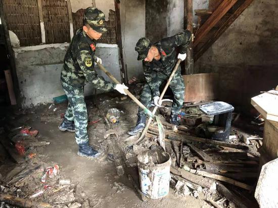 武警温州支队官兵手拿铁锹、扫把等清扫工作,逐家逐户进行清理打扫,帮助村民重建家园。温州武警供图