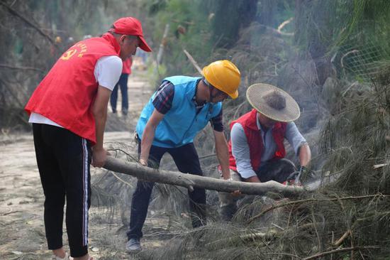 图为:13日,浙江省温岭市城南镇志愿者正对主干道进行疏通清理 金云国 摄