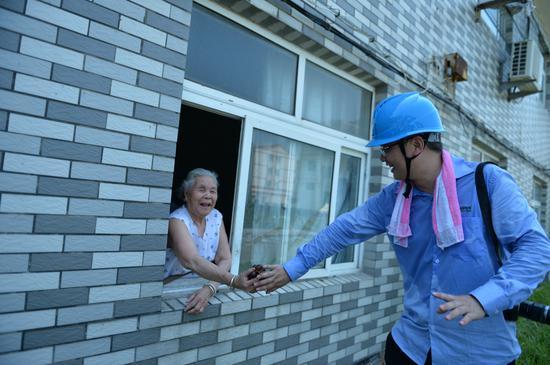 孙婆婆从窗口给电力抢修队队员递葡萄。  国网海宁市供电公司供图