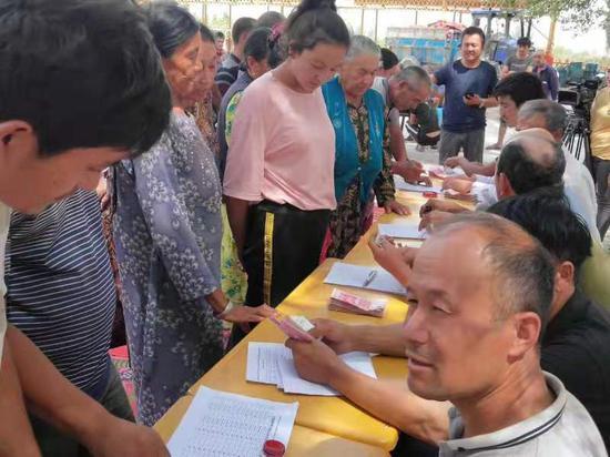 图为2018年年终,巴楚县琼库尔恰克乡阿克托格拉克村农民专业合作社为土地入股的农民现场分红。王二民 摄