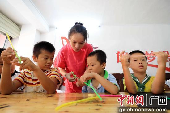 """8月17日,在广西柳州市融安县""""老乡家园"""",美术老师侯丽珍在""""七彩假期""""课堂上教孩子们做手工。谭凯兴 摄"""