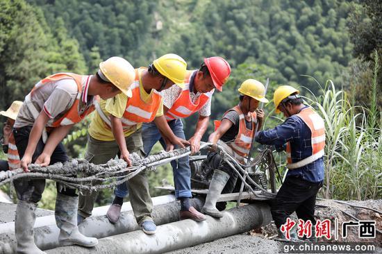 8月13日,融水苗族自治县境内的罗融二级公路施工路段,工人们正冒着37℃的高温在进行作业。