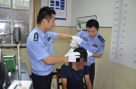 工作人员对吸毒人员进行毛发检测。警方 供图