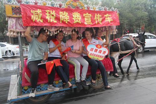 图为鄯善县税务局减税降费宣传小分队在当地特色马车上设立税收政策咨询台。