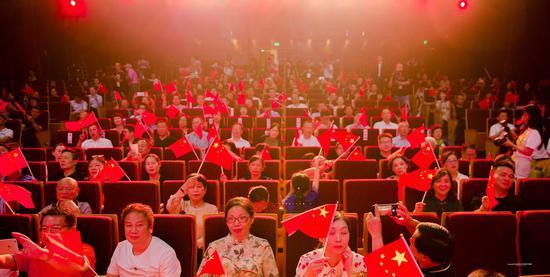 活动现场观众集体挥舞手中小国旗。卢简明 摄