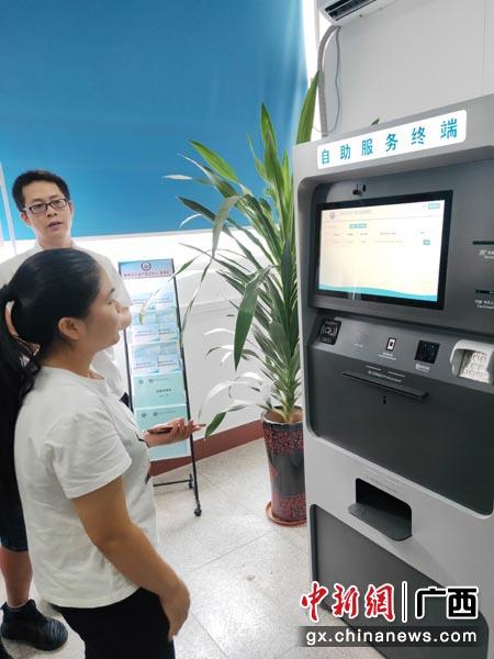 图为市民使用不动产自助服务系统办理业务。