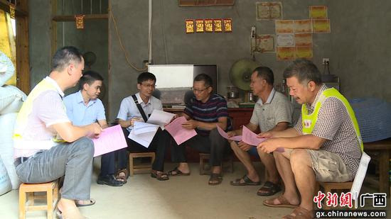 广西鹿寨农村商业银行的工作人员上门为贫困户办理小额信用贷款。