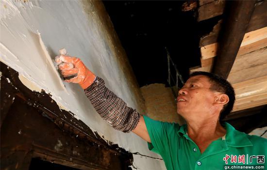 在融安县大坡乡福下村红专屯,一名工人在刮腻子。覃庆和  摄