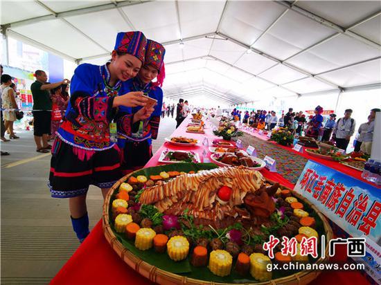 被毛南山乡精美菜品吸引的壮乡少女在拍照。