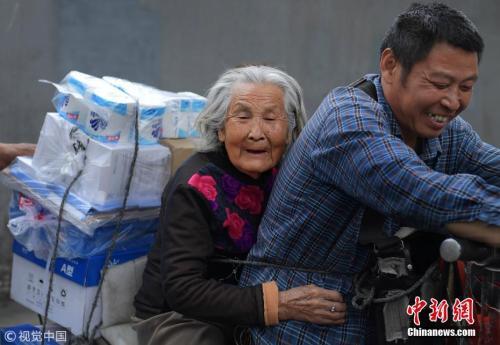 资料图:2018年4月,成都,为了尽孝谋生两不误,53岁的货郎蔡玉俊,每天驮着92岁身患老年痴呆的母亲,穿梭在成都大街小巷。 图片来源:视觉中国