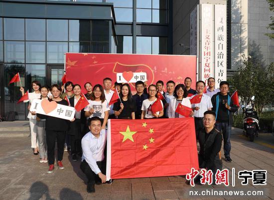 青年代表挥舞国旗,向新中国成立70周年献上祝福。