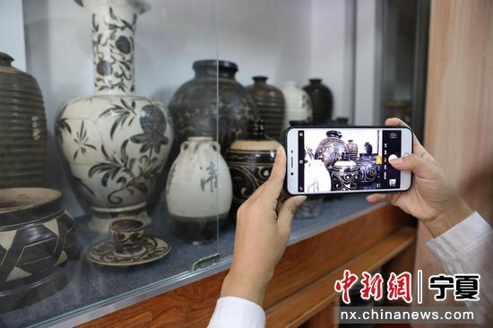 市民用手机记录佑啟堂收藏的陶瓷。