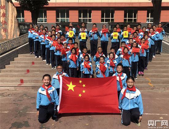 """乌鲁木齐市第四十九中学""""我和国旗合个影·我为祖国送祝福""""快闪活动中,同学们手举国旗,摆出""""心""""型。"""