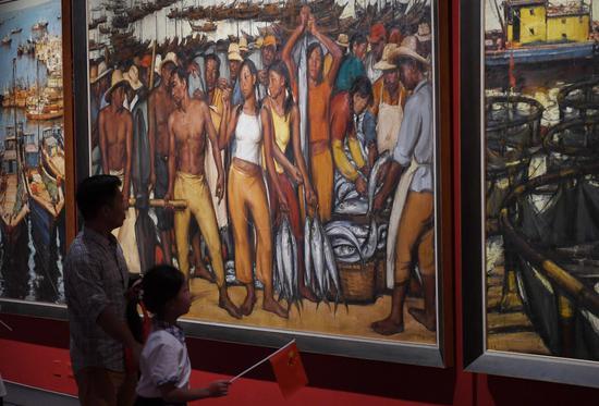 图为:两位市民在参观作品《舟山渔场》。王刚 摄