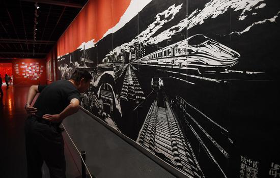 图为:参观者驻足参观作品《最前线》。王刚 摄