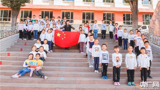 """乌鲁木齐市第四十九中学""""我和国旗合个影·我为祖国送祝福""""快闪活动中,老师和同学们摆出""""70""""字样,庆祝新中国成立70周年。"""