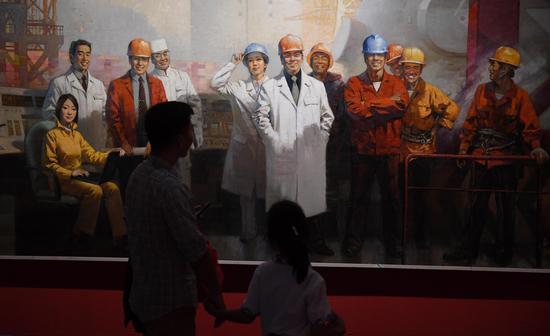 图为:两位市民在参观作品《核电之光》。王刚 摄