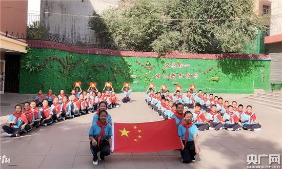 """乌鲁木齐市第四十九中学""""我和国旗合个影·我为祖国送祝福""""快闪活动中,同学们手举国旗,摆出""""十一""""字样。"""