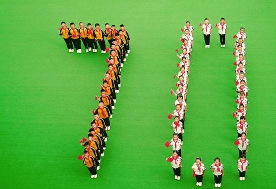 """同学们穿着漂亮的校服,戴着鲜艳的红领巾,摆出""""70""""和""""爱心""""的造型,齐心祝福祖国,向祖国深情告白。"""
