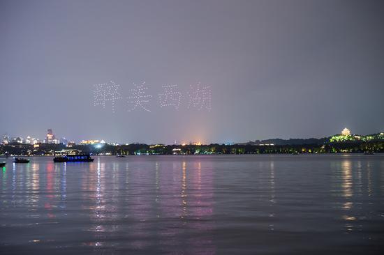 """平湖秋月水域上空近300架无人机灵动地变换着队形,摆出""""醉美西湖""""字样 西湖景区管委会提供"""
