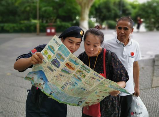 图为:阿色亚•买门为游客提供咨询服务。景区行政执法局