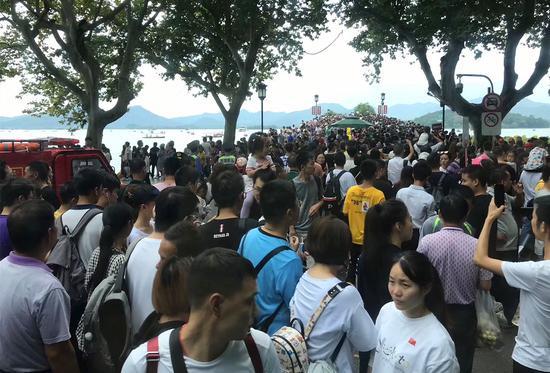 """图为:""""黄金周""""期间杭州西湖断桥口的游客。景区行政执法局"""